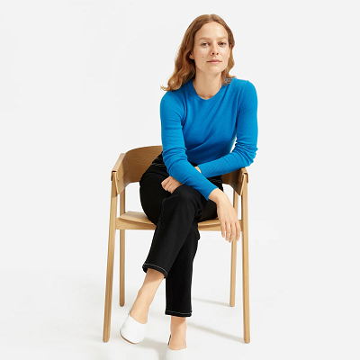 woman sitting on a stool in a blue sweater