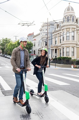 man and woman riding electric scooter
