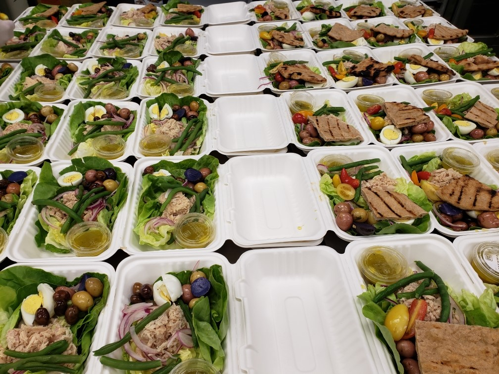 six rows of lunch boxes in biodegradable packaging filled with green veggies, olives, pita, and onions.