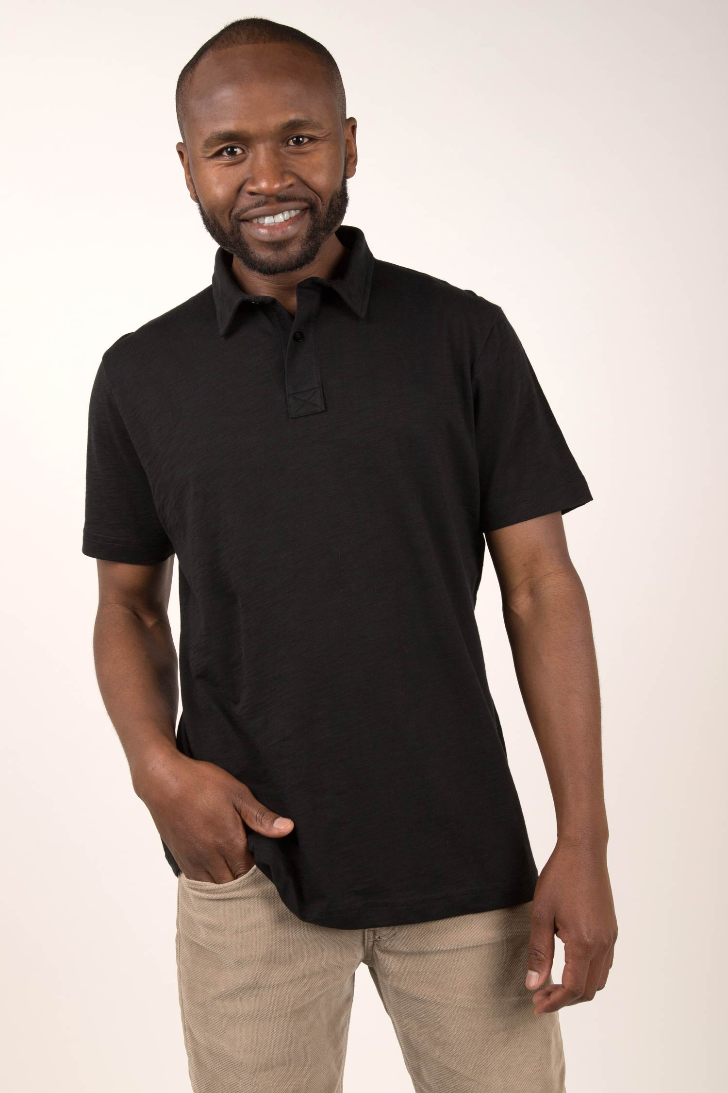 Black male model smiling at camera wearing a Black alpaca wool sub polo shirt. He has one hand in his pocket and is leaning on his right leg.