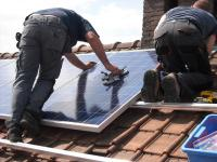 workers attaching solar panels to a house