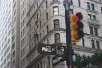 "black street pole with street light and street sign saying ""Wall St"" against the backdrop of a tall, grey building with lots of windows"
