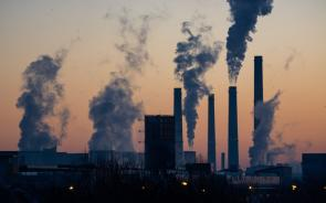 energy plants emitting clouds of pollution against sunset