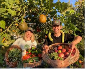 John and Holly in their Climate Victory Garden with baskets of vegetables