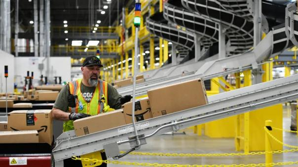 man working in Amazon plant with packages