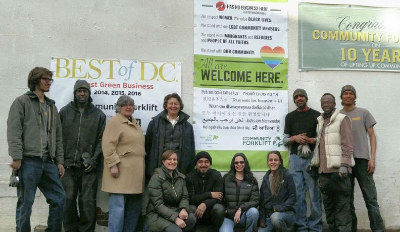 The Main Street Alliance is urging businesses nationwide to print out and display its anti-hate posters in their offices and shop-fronts. Community Forklift turned theirs into a huge banner, seen here hagning in front of their Maryland warehouse store with several employees. Photo courtesy of Community Forklift.