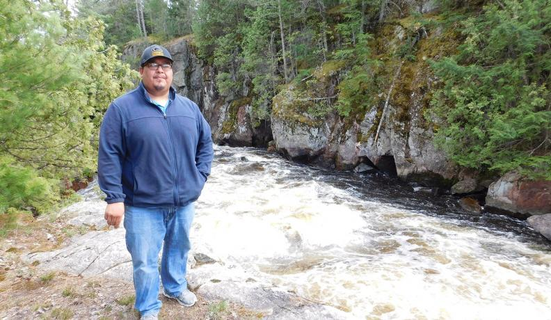 Guy Anahkwet Reiter stands near the Menominee River, which is sacred to the Menominee Tribe.