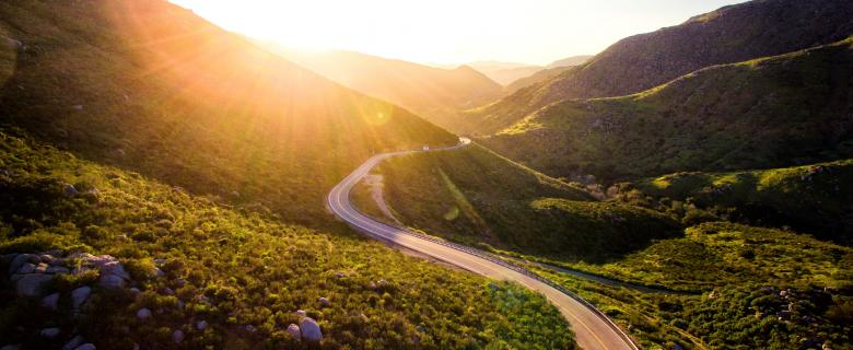 a road winding through the green California hills into the sunrise