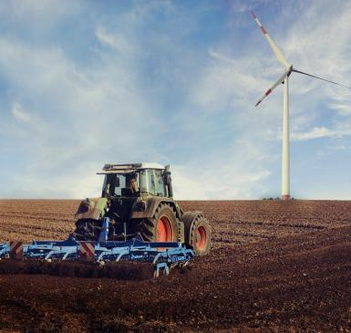 Image: tractor on a field with a wind turbine. Regenerative Agriculture.