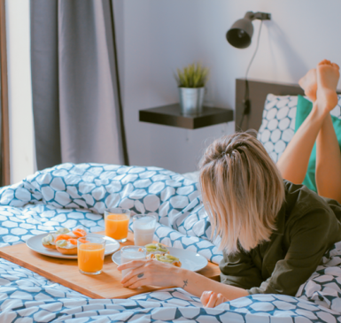 Person on bed facing a tray of food