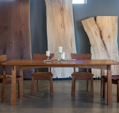 TY Fine Furniture table in front of wood slabs