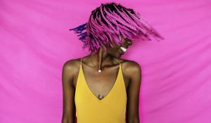 girl shaking her pink hair in front of a pink background