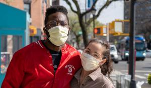 couple poses on the street with masks