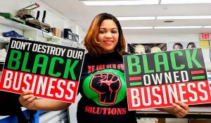 "Keeanna Barber of WDB Marketing holds signs that say ""Don't destroy our Black Business"" and ""Black Owned Business"" that she printed at her shop."