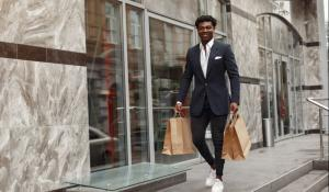 black man in suit walking with paper bags in hand.