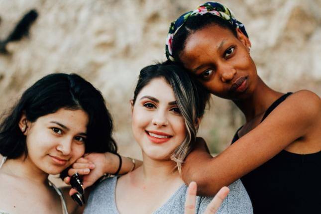 Portraiture of three diverse women leaning on each other's shoulders. The one in the middle is throwing up a peace sign.