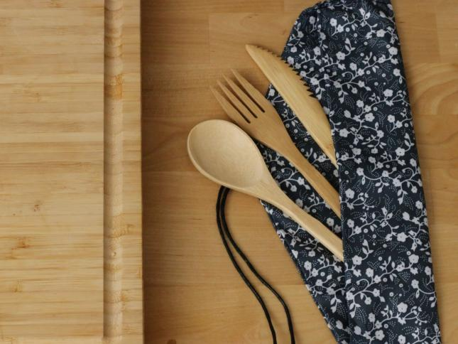 Reusable bamboo cutlery in navy blue cloth wrapping next to a cutting board