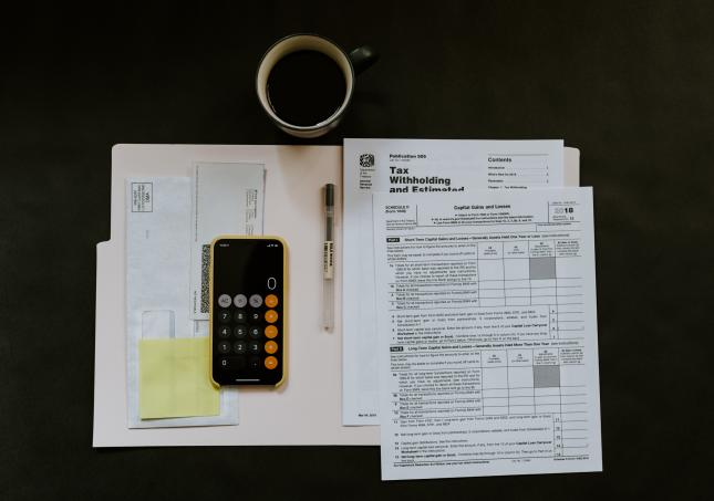 Overhead view of a manila folder containing tax documents, envelopes, and a calculator on top of a black desk next to a coffee mug