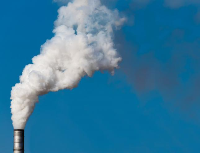 smoke billowing out of a factory chimney against a blue sky