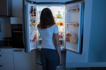 girl looking in fridge at night